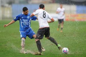 Franco contende ad un avversario il possesso su un campo reso pesantissimo dalla pioggia (foto Paolo Furrer)
