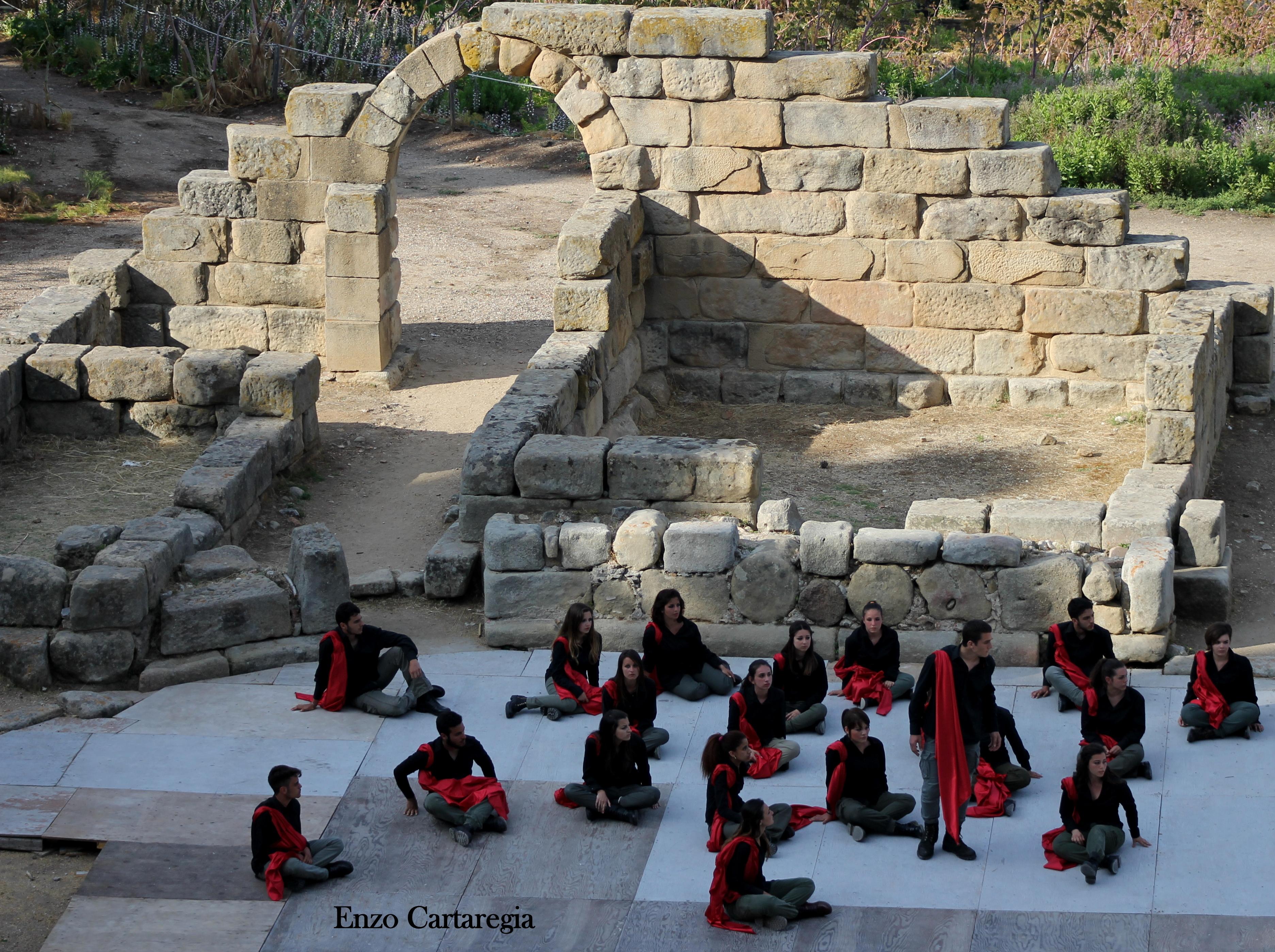 Una scena de L'Iliade, sullo sfondo i ruderi di Tindari